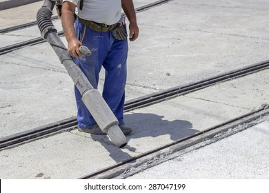 Worker with leaf-blower, cleaning out the dust for better asphalt adhesion, during tram track renewal works.