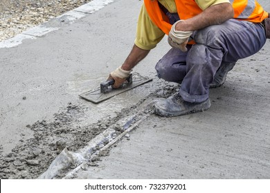 Worker leveling concrete with trowel, hands spreading poured concrete.
