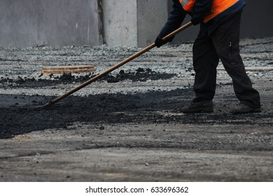 The worker is leveling the crumb of asphalt in the pit with a drag-roller before the paving with a road mini building roller