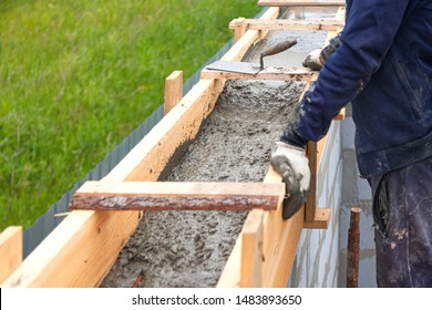 Worker levels concrete in formwork using a trowel