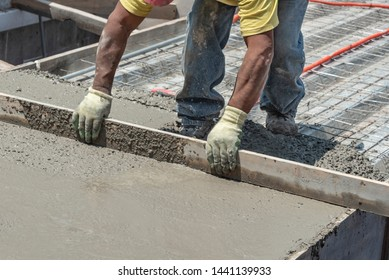 Worker levels a floor cement mortar. Using a straight wooden board to level a rooftop