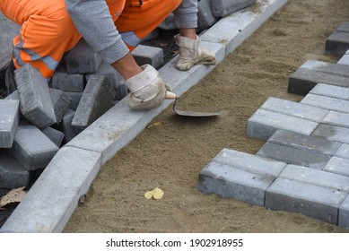 A worker levels the sand, laying paving slabs. Construction of a road for pedestrians.