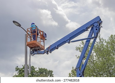 Worker in lift bucket during installation of metal pole with street lamp, street light pole with double head.