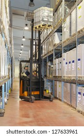 Worker load goods with forklift in warehouse