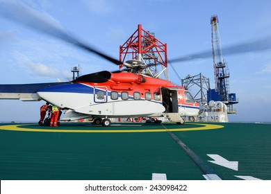The worker are loading baggage of passenger to helicopter at oil rig platform