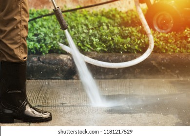 Worker in long boots cleaning driveway with gasoline high pressure washer splashing the dirt. High pressure cleaning,lower body.Professional cleaning services.