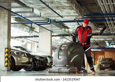 worker with machine cleaning floor in parking garage.