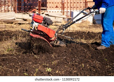 Worker with a machine cultivator digs the soil in the garden