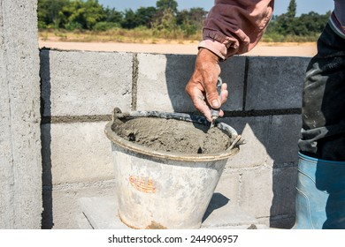 worker make concrete wall by cement block and plaster at construction site