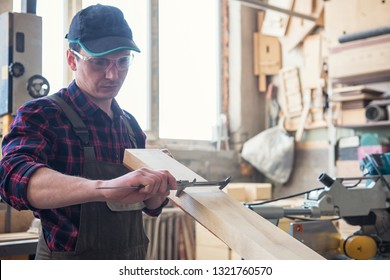 The worker makes measurements of a wooden board with corner ruler.