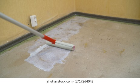 Worker making apartment renovation. Male specialist processing concrete in new apartment. Home improvement concept. The process of priming the floor with a special building primer in white