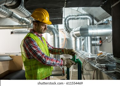 Worker making final touches to HVAC system. HVAC system stands for heating, ventilation and air conditioning technology. Team work, HVAC, indoor environmental comfort concept photo.