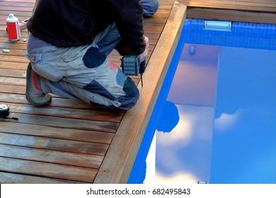 Trabajador haciendo hoyos en la cubierta de madera de la piscina con la máquina de taladros.
