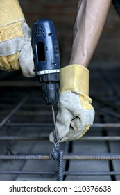 worker making reinforcement metal framework for concrete pouring with Cordless drill