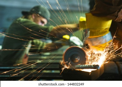 Worker making sparks while welding steel