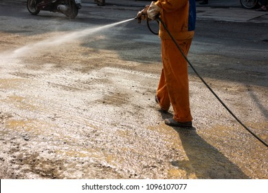 Worker making street wet with water spray at construction area