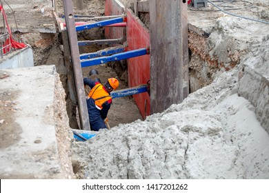 Worker making trench bed for new pipeline construction. Trench preparation for buried pipes. Keeping workers safe during trenching and excavation.