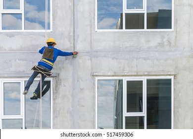 The worker man abseiling with rope on construction site