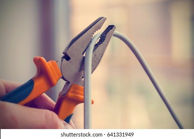 Worker man cutting electric wires with pliers