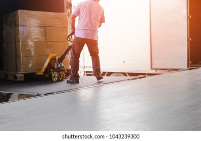 Worker man dragging hand pallet truck or manual forklift with the shipment pallet unloading from a truck.