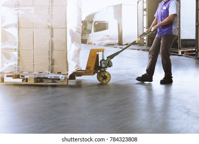 Worker man dragging manual forklift pallet shipment into container a truck