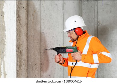 A Worker man drilling in concrete on a construction site