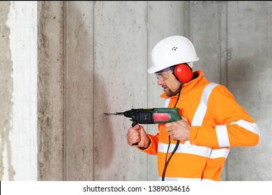 Un trabajador perforando en concreto en un sitio de construcción