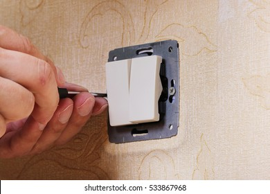 Worker man electrician is repairing damaged switch in the apartment, installation of new closeup