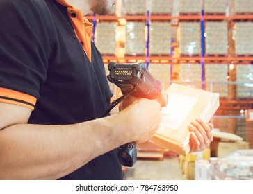 Worker man hand holding a barcode scanner and scanning package in warehouse distribution