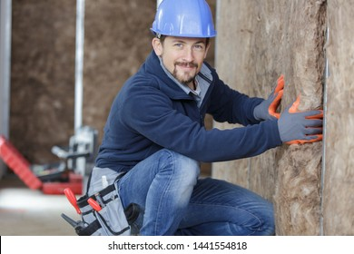 worker man insulates a wall