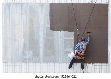Worker man insulates wall high-rise building