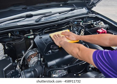 Worker man open the car hood and polishing car with microfiber cloth ,vintage style