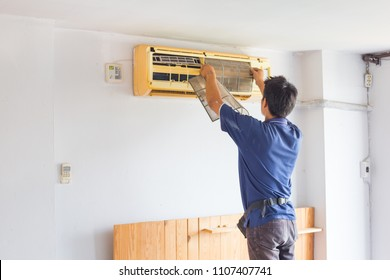 Worker man repiaring and cleaning home air conditioner