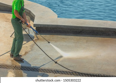 Worker man in uniform washes street or park sidewalk near water pool or fountain. Municipal service of city cleaning process. Guy uses spray equipment