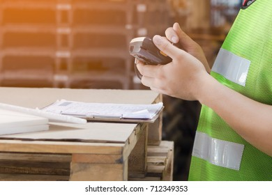 Worker man using RFID scanner in a warehouse. He standing hold a device and put a paper on the pallet.