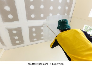 A worker man using roller on a long stick is painting the ceiling of a new buliding house. Home impovement and new house construction concept.