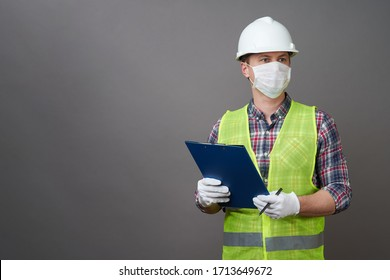 Worker man wearing face mask and protective hard hat. Young engineer worker wear a white helmet and medical mask. Coronavirus Hygiene, safety concept