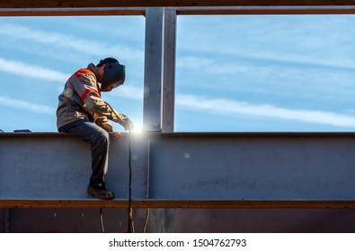 Worker Man welder in uniform of a welder sitting on an iron support welds an iron beam against the sky