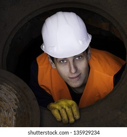 Worker In the manhole, looking directly at the camera. Serbia / Manhole