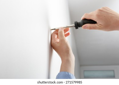 Worker manually tightening an artwork hang screw into a drilled hole in white wall with screwdriver, renovating, decorating and improving home. Do-it-yourself (DIY) concept.