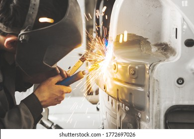 Worker in mask welds car in auto service of bodywork.
