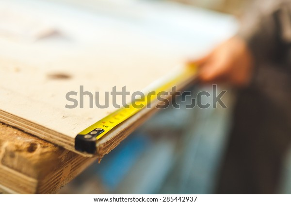 Worker measures wooden deck with tape measure in workshop. Selective focus photo