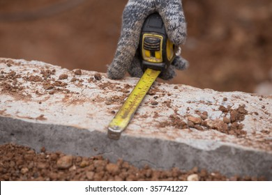 worker measuring concrete at construction site with tape measure