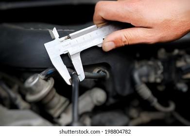 Worker measuring diameter in auto repair service