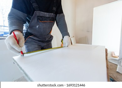 Worker is measuring the plastic detail before it cutting in apartment that is under construction, remodeling and reconstruction. Concept of total home improvement
