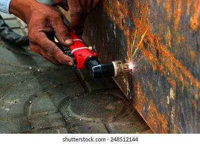 worker Metal Cutting large steel with Plasma cutters, Workman is working by use Plasma cutters the iron in building, Spark splash around the ground.