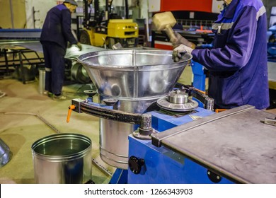Worker in metalworking plant finishing of forming pipe part for construction of ducts of industrial air condition system