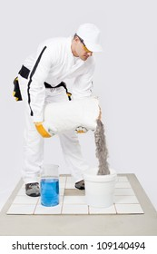 Worker mix tile adhesive bucket  of water white tiles