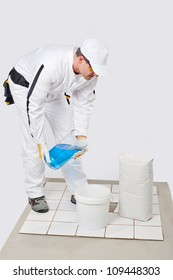 Worker mix tile adhesive in bucket of water with product package
