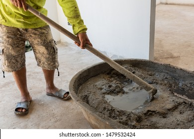 Worker mixing cement mortar at construction site
